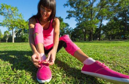 Photo pour Chaussures de course - femme attacher les lacets de chaussures. Gros plan de coureur de remise en forme sport féminin se prépare pour faire du jogging en plein air sur la forêt. - image libre de droit