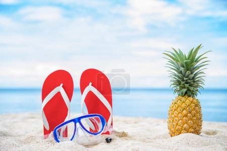 Photo for Pineapple, mask and filp flop on the beach - Royalty Free Image