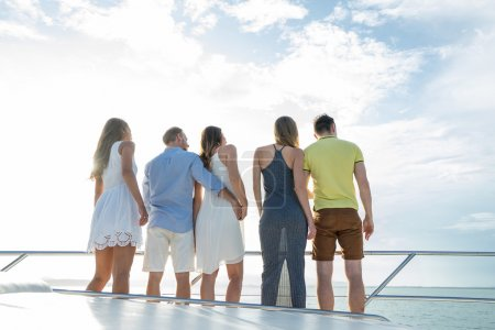 Group of  people looking outside from yacht.