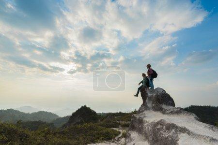Photo pour Jeunes randonneurs profitant d'une vue sur la vallée depuis le sommet d'une montagne au coucher du soleil. Concept de voyage . - image libre de droit