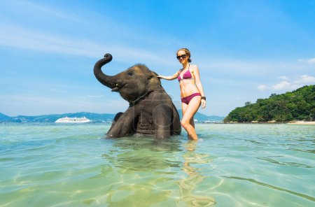 Woman and elephant in ocean