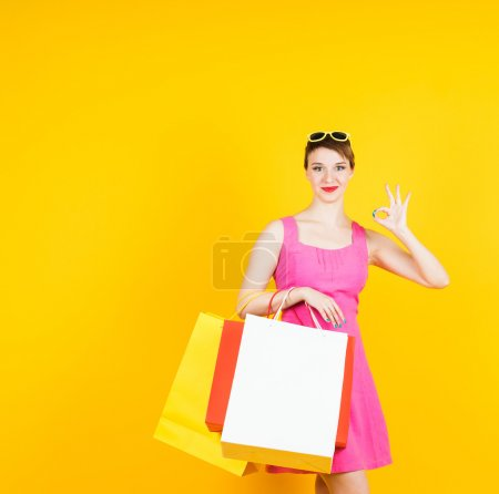 Photo for Smiling beautiful woman with shopping bags showing OK on yellow background - Royalty Free Image
