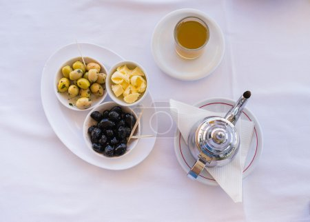 Photo for Traditional moroccan mint tea with olive on the table. Overhead close up view. - Royalty Free Image