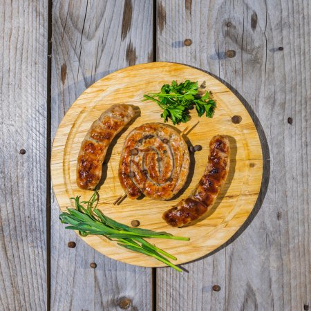 Photo for Grilled sausages served on wooden plate over wooden table. Overhead close up shot. - Royalty Free Image