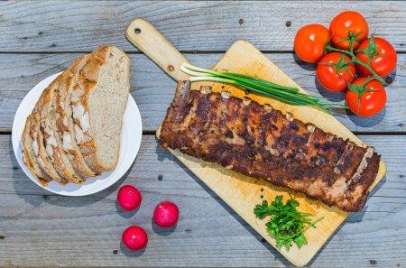 Photo pour Côtes levées grillées servi sur plaque en bois au-dessus d'une table en bois avec légumes et pain sur fond. Prise de vue aérienne. - image libre de droit