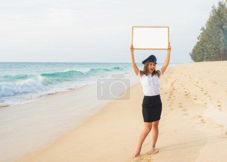 Photo pour Concept de voyage. Agent de bord attrayant avec valise, chapeau et tableau blanc sur la plage . - image libre de droit