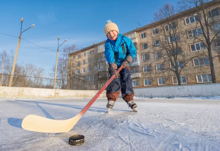 Young smiling boy playing ice hockey