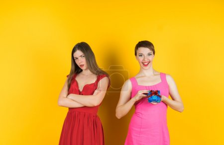 Photo for The girl received a gift, and the other girl looks with angry. Isolated studio yellow background female model. - Royalty Free Image