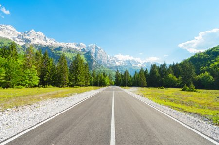 Road in forest to Mountain with snow-capped peaks....