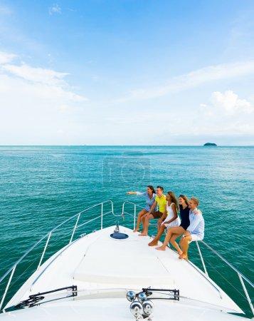 Foto de Amistad y gente joven feliz sittingon el yate de cubierta mirando y apuntando a navegar el mar. - Imagen libre de derechos