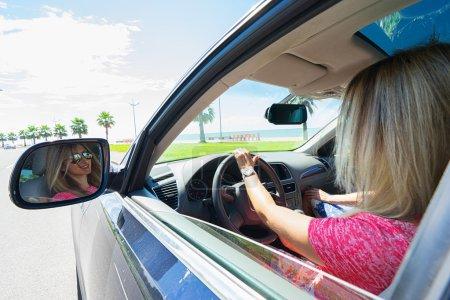 Photo pour Heureuse jeune femme conduire une voiture avec raflecion de visage sur le miroir. Mettre l'accent sur les miroirs. - image libre de droit