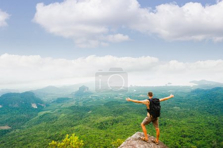 Photo for Hiker standing with raised hands and enjoying a beautiful nature from top of mountain. - Royalty Free Image