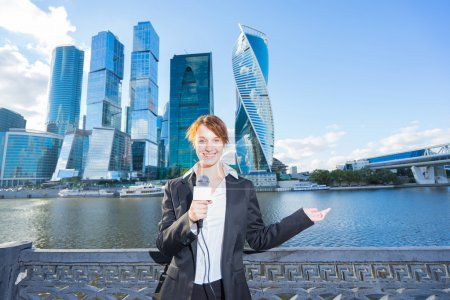 Photo for Smiling woman in business suit holding a microphone conducting a business interview, journalist reporting, public speaking, press conference.  Skyscrapers  and river on background - Royalty Free Image