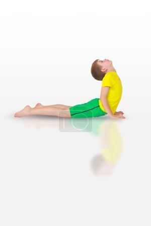 Little boy doing yoga on white background...