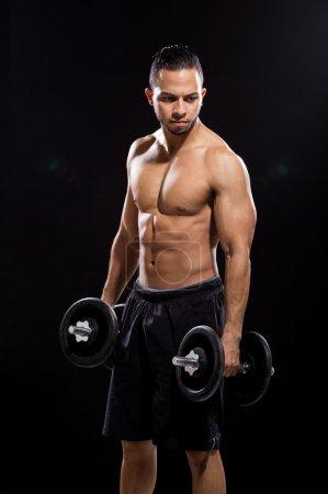 Fitness model holding dumbbell on black background