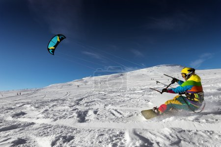 Snowboarder with kite riding very fast