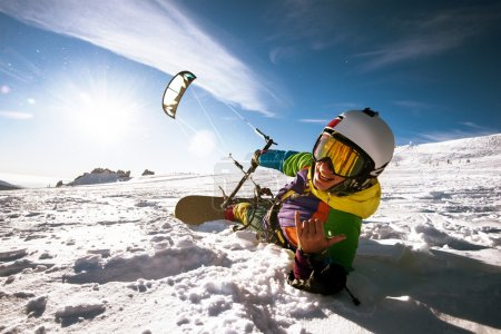 Snowboarder with kite lies on the snow