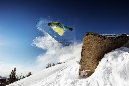 Snowboarder jumps from big rock
