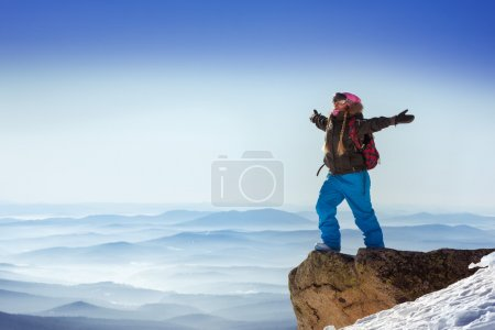 snowboarder stands on big rock