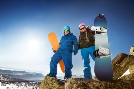 couple of snowboarders stands on big rock