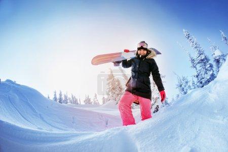 Girl snowboarder goes through snowdrift