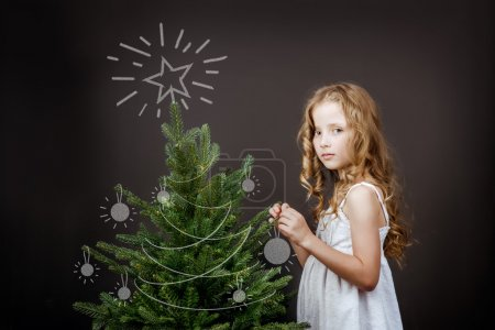 girl stands near Christmas tree
