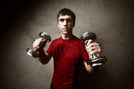 Muscle man posing with dumbbells