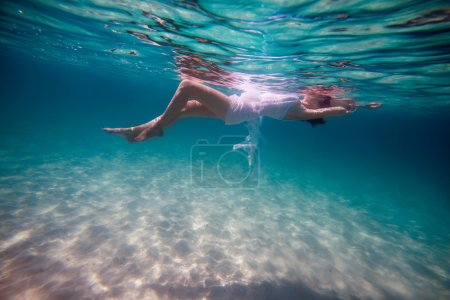 Photo for Slim beautiful girl lying on the waves on underwater background - Royalty Free Image