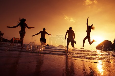 Happy friends running on a beach. Travel concept