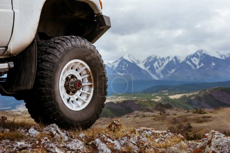Big car wheel on background of mountains