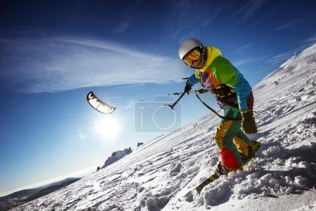 Happy snowboarder with snowkite stands in snowdrift
