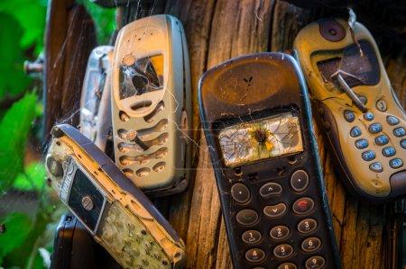 Photo pour Les vieux téléphones portables sont cloués sur un coffre. Les téléphones portables gravement endommagés transfèrent le message que les téléphones doivent être éteints ici . - image libre de droit