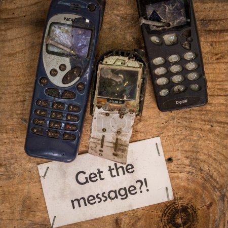 Photo pour Les téléphones portables ne doivent pas être utilisés dans cet endroit. Recevez le message - Trois vieux téléphones cellulaires sont cloués et endommagés. Une note clarifie le message - image libre de droit