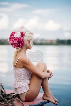 young blond woman sitting on the yacht