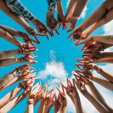 Photo for Hands showing peace sign forming a circle with sky on the background - Royalty Free Image