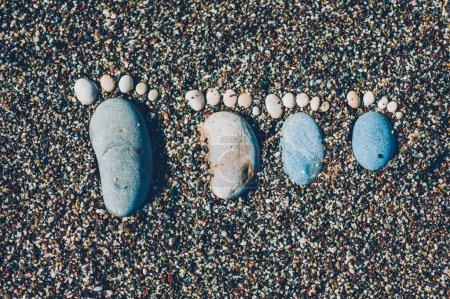 Photo pour Pieds nus trace en pierres de galets sur la surface fond de plage côte sable vue de dessus - image libre de droit