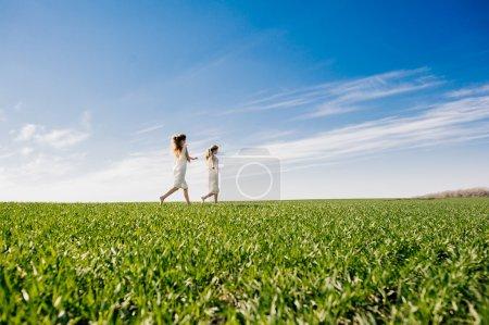 deux soeurs jumelles blondes sur pelouse