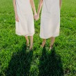 Legs and hands of two twin blond sisters on the la...