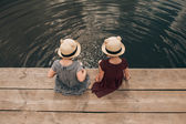 Young girls dipping feet in the lake