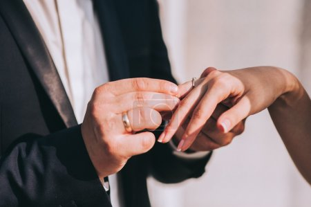 groom put wedding ring on bride