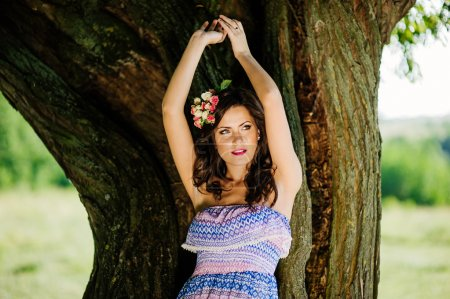 femme qui pose sur la pelouse près de vieil arbre