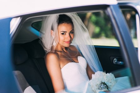 Beauty bride in bridal gown in a car