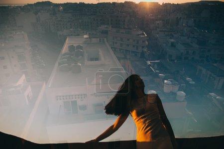 jeune fille debout au coucher de soleil