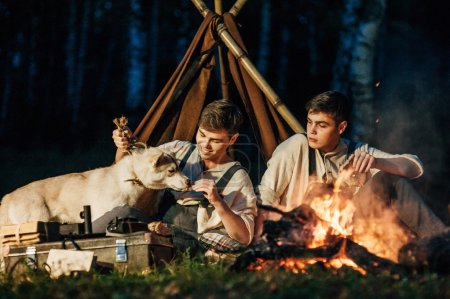 two twin brothers sitting around a campfire