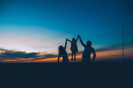 Photo for Happy family together, parents with their little child at sunset, father raising baby up in the air - Royalty Free Image