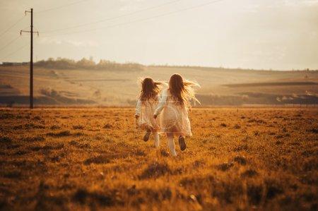Photo pour Deux petites sœurs jumelles prêtes à rencontrer le coucher du soleil - image libre de droit