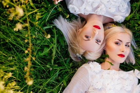 Twins sisters lying on green grass