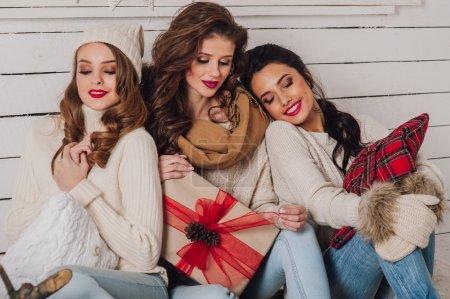 Three beautiful girls with gift box