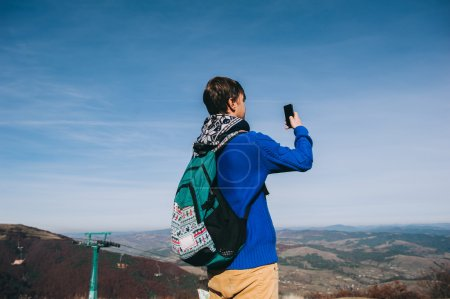 Young hipster taking photo at mountain