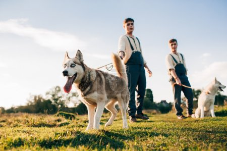 two twin brothers with husky dogs